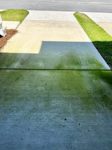 Driveway with green stains before washing by Camelot Pressure Washing in Harrisburg, NC